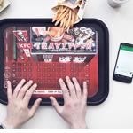 Papieren toetsenbord gaat vette vingers op telefoon tegen
